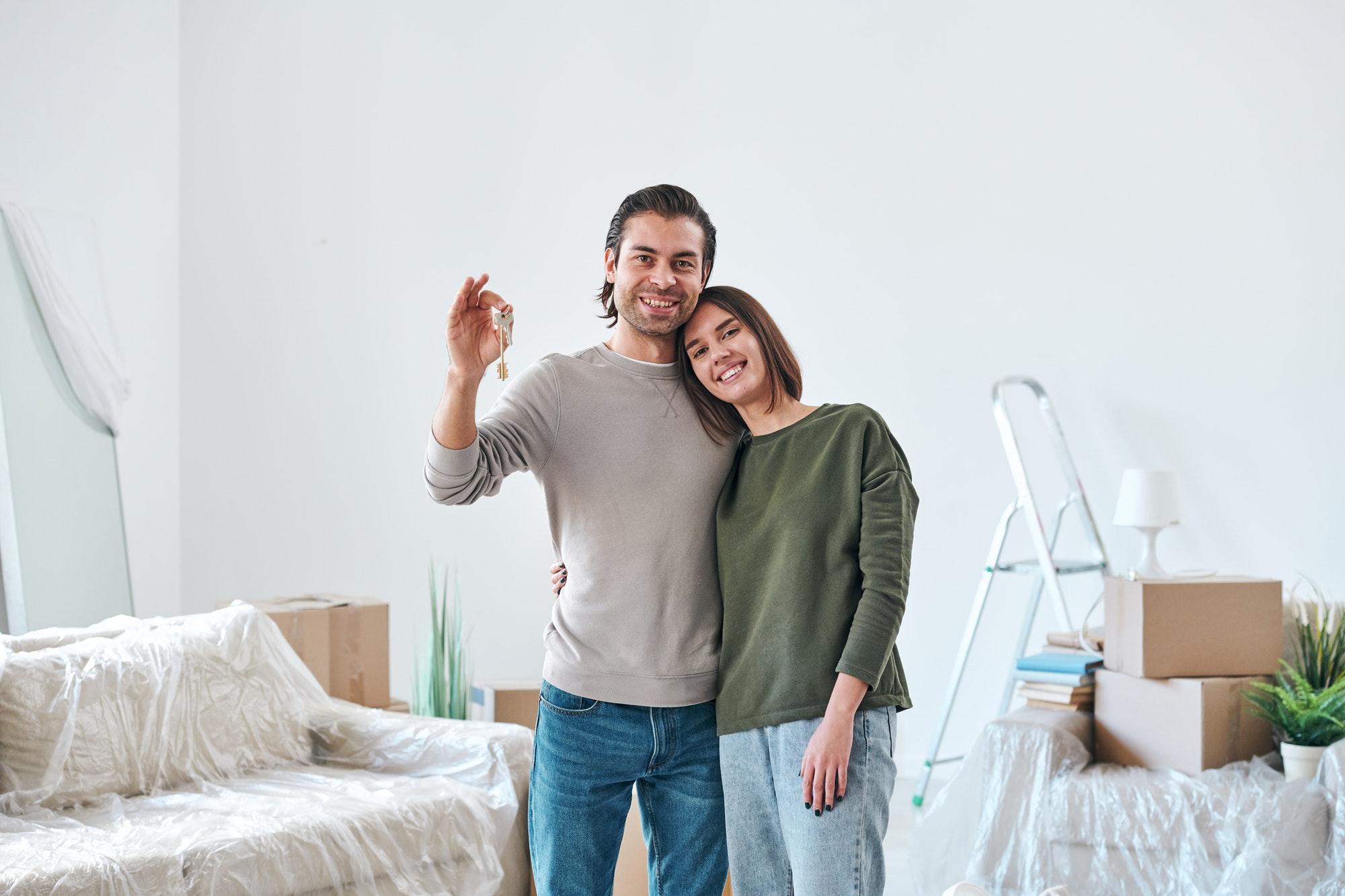 Young affectionate woman embracing her husband with key to their new house